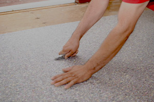 TCB Carpets' Installer Cutting Carpet Pad